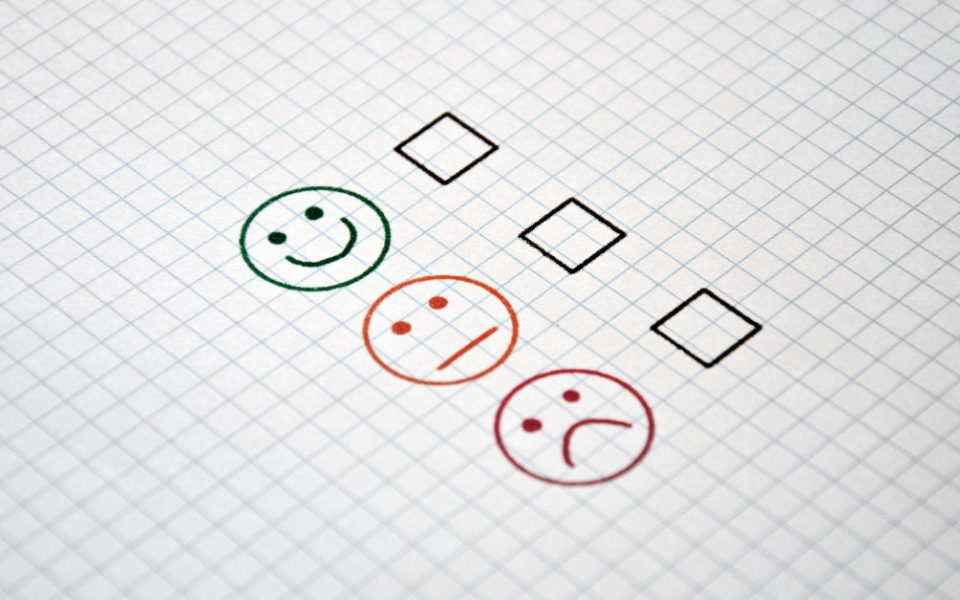 A drawing of a happy face, a neutral face and a sad face with a en empty tick box next to each