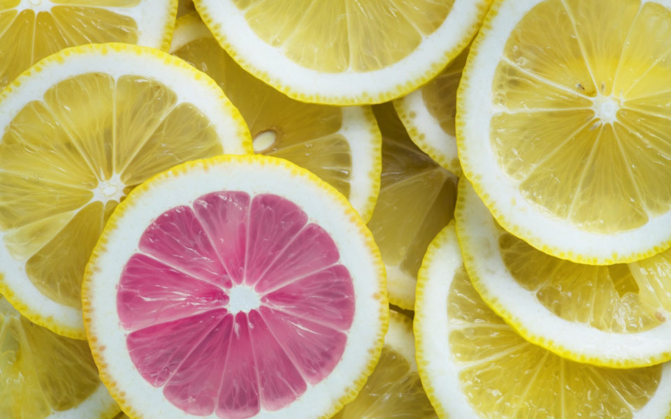 A slice of pink grapefruit amongst slices of lemon, highlighting the unique colour.