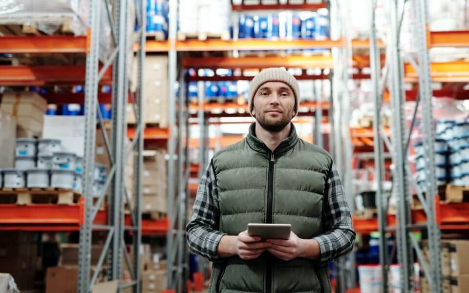 A photograph of a man holding a tablet computer in a warehouse.
