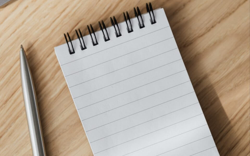 An image of a notepad and pen