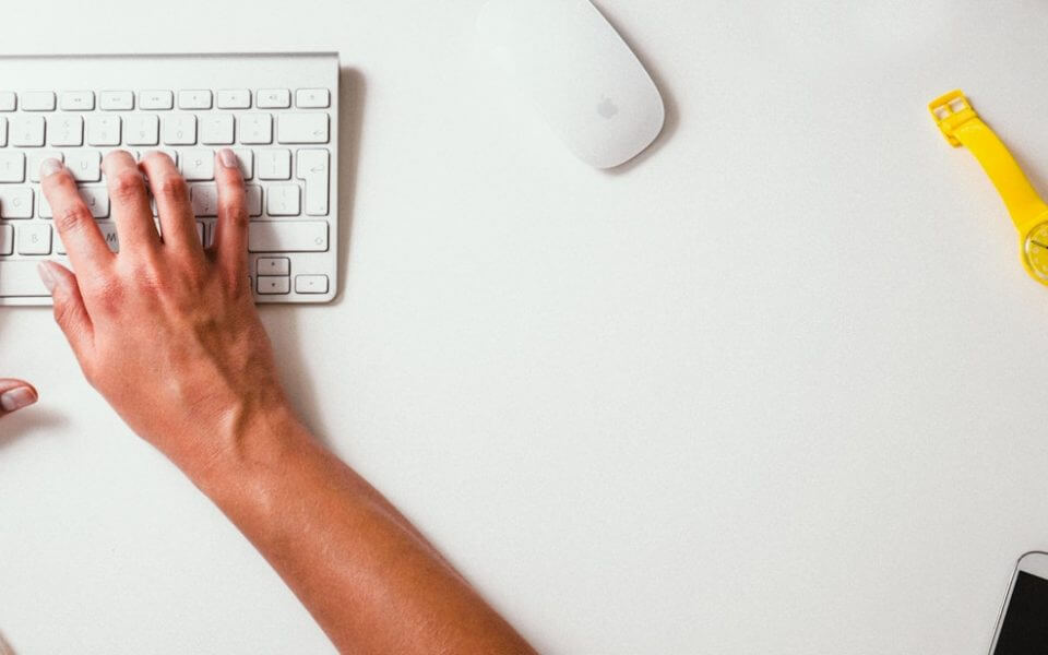 A photo of a person typing on a white keyboard